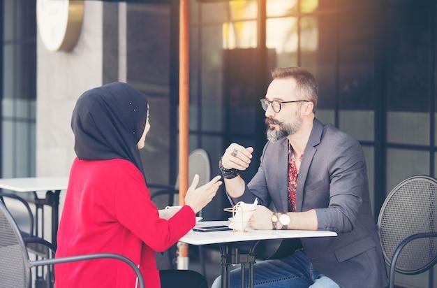 Азиатская мусульманская бизнесвумен в кафе разговаривает с клиентом или другом парня