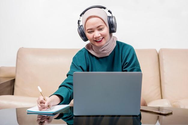 Asian muslim businesswoman using a laptop working from home. prevent flu disease coronavirus