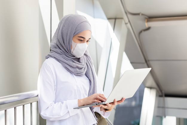 Asian muslim businesswoman wearing medical mask for prevent dust and infection virus working with laptop on the way go to office.