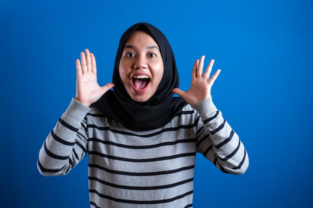 Asian muslim college student girl shows surprised or shocked expression with open mouth
