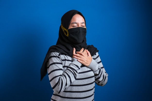 胸に痛みを感じるマスクを身に着けているアジアのイスラム教徒の大学生の女の子、左胸を保持するジェスチャー。青い背景