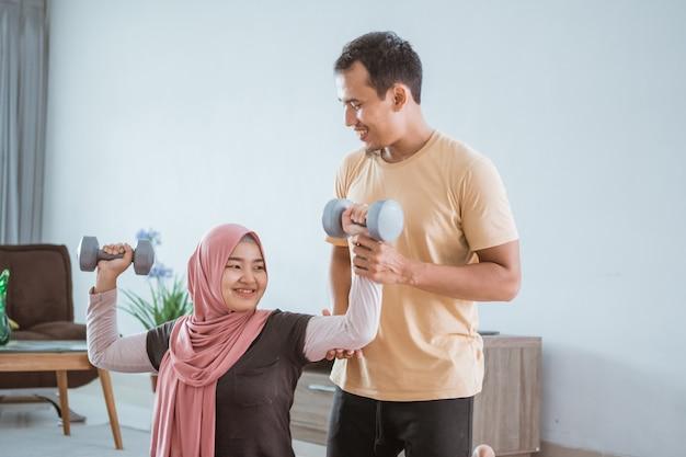 自宅でエクササイズとウェイトリフティングをしているアジアのイスラム教徒のカップル。夫は妻のトレーニングを手伝っています