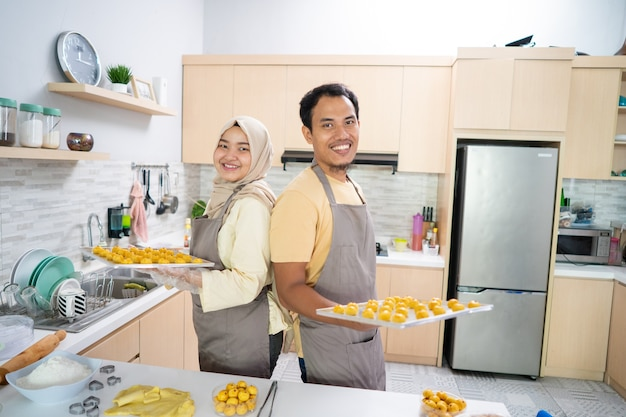 Азиатская мусульманская пара вместе готовит закусочный торт настар на кухне во время рамадана для праздника ид празднования