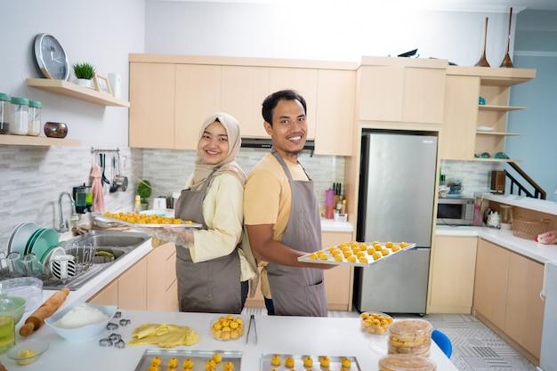 Азиатская мусульманская пара вместе готовит закусочный торт настар на кухне во время рамадана на праздник мубарак с семьей. индонезийская кухня традиционная