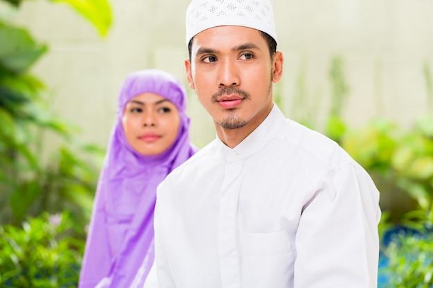 Asian muslim couple, man and woman, praying at home
