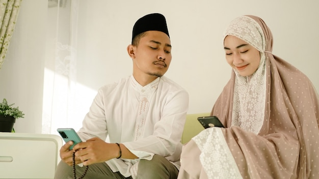 Asian muslim couple playing cell phone on sofa
