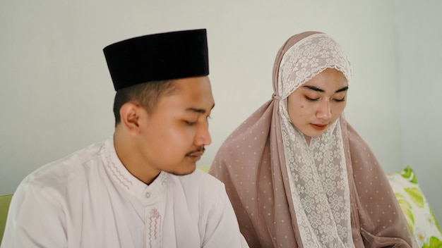 Asian muslim couple praying together at home