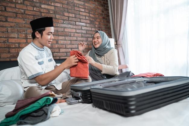 アジアのイスラム教徒のカップルが服とスーツケースを準備します。