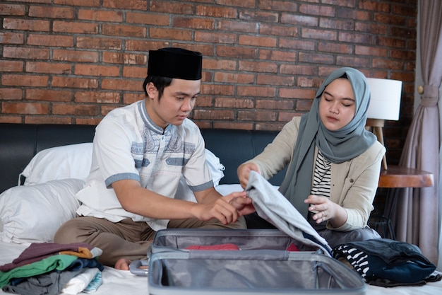 Asian muslim couple prepare clothes and suitcase