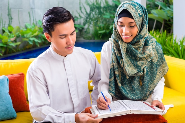 Asian muslim couple reading together koran or quran