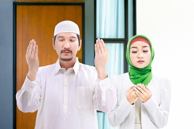 Азиатская мусульманская пара стоя, подняв руки и вместе молясь дома