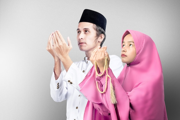 Asian muslim couple standing while raised hands and praying together with gray wall background