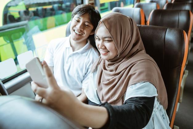 아시아 무슬림 커플은 버스에 앉아 셀카를 함께 찍는 동안 휴대폰 카메라에 미소를 짓는다