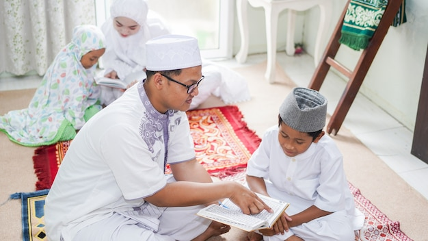 Asian muslim families read the quran after prayers