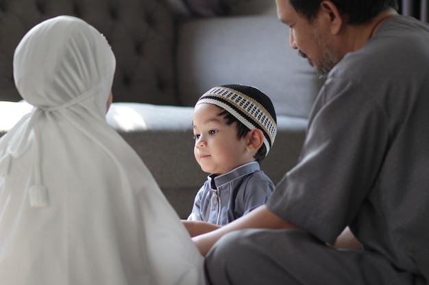 Азиатская мусульманская семья в традиционных костюмах. отец-мусульманин с детьми в их доме после молитвы к богу. концепция мусульман в священный месяц рамадан.