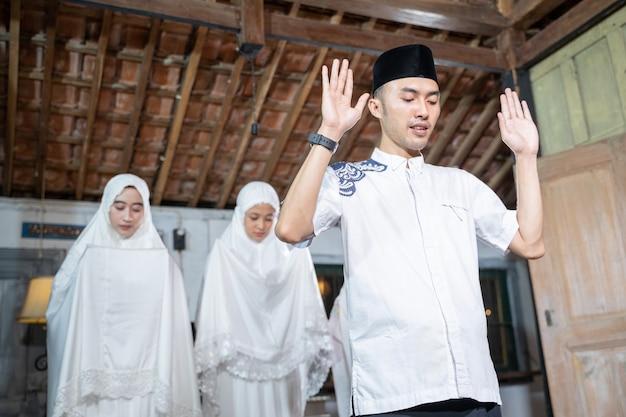 집에서 함께 jamaah기도 아시아 이슬람 가족. 흰색과 히잡을 입고 sholat 또는 salah