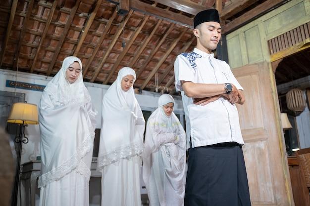 Азиатская мусульманская семья молится вместе дома. шолат или салах в белом и хиджабе