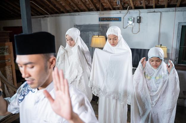 Азиатская мусульманская семья молится вместе дома