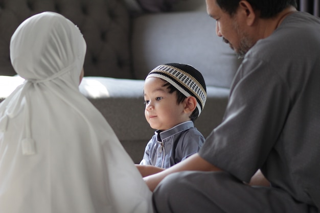 Asian muslim family in traditional costume.muslim father with kids in their house after pray to god.concept of muslim people in ramadan holy month.