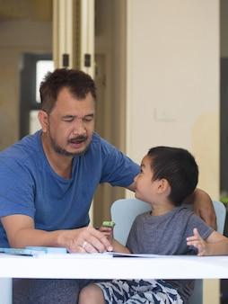 아시아 무슬림 아버지는 작은 유치원 아들에게 글쓰기를 가르칩니다. 연필 그립을 사용하는 소년과 그의 순간을 즐기십시오. 아버지와 아들의 개념.