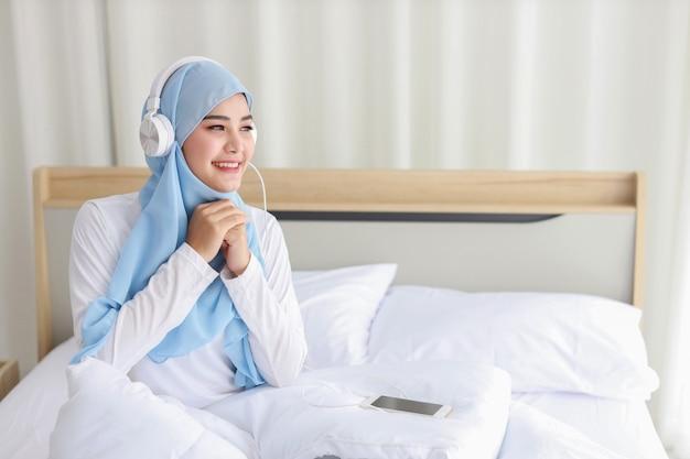 携帯電話でオンラインストーリーを見ているパジャマのアジアのイスラム教徒の女性は、ベッドに横たわって、ワイヤレスインターネットに接続されています。