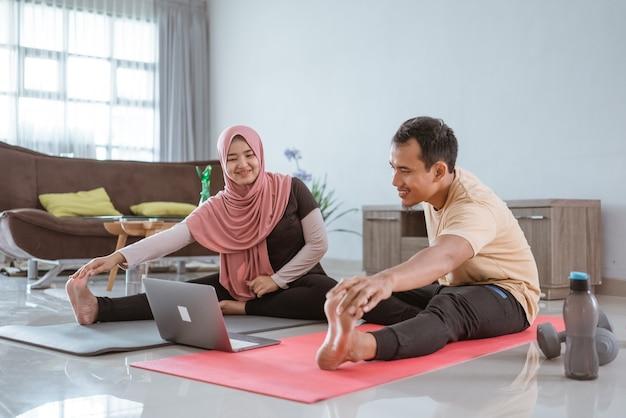 ストレッチとラップトップを介してオンラインビデオチュートリアルを見ているアジアのイスラム教徒のフィットネスカップル