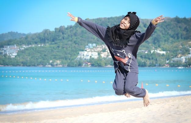 アジアのイスラム教徒の少女はヒジャーブを着て、ビーチでジャンプしています