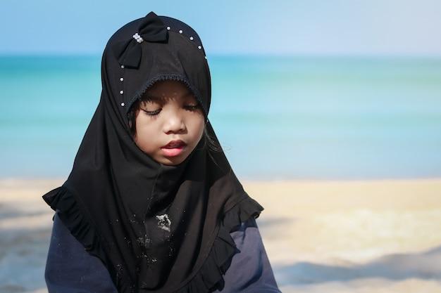 ビーチで休暇中にヒジャーブを身に着けているアジアのイスラム教徒の少女