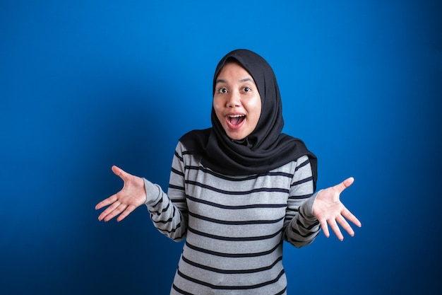 Asian muslim girl wearing hijab shows surprised or shocked expression with open mouth, close up facial expression over blue background