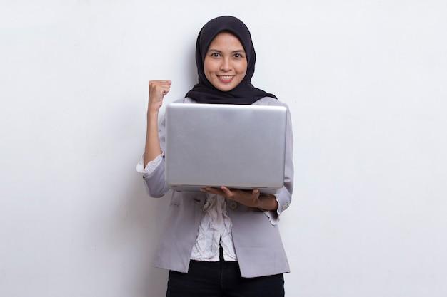 흰색 배경에 격리된 노트북 컴퓨터를 사용하는 아시아 이슬람 히잡 여성