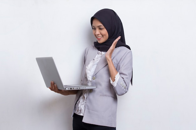 Asian muslim hijab woman using her laptop computer isolated on white background