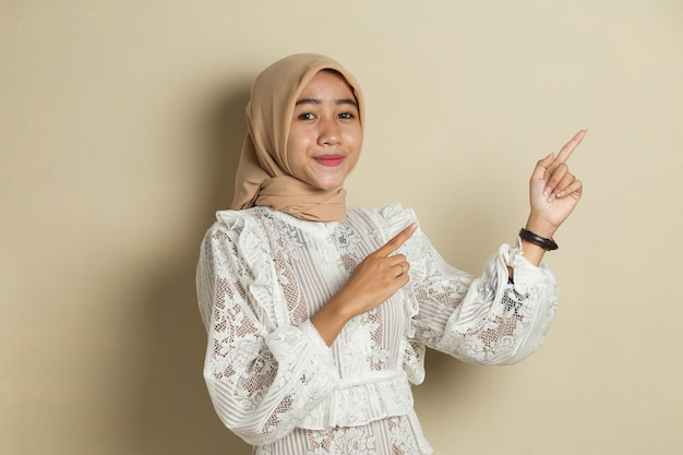 Asian muslim hijab woman with hand point on empty space