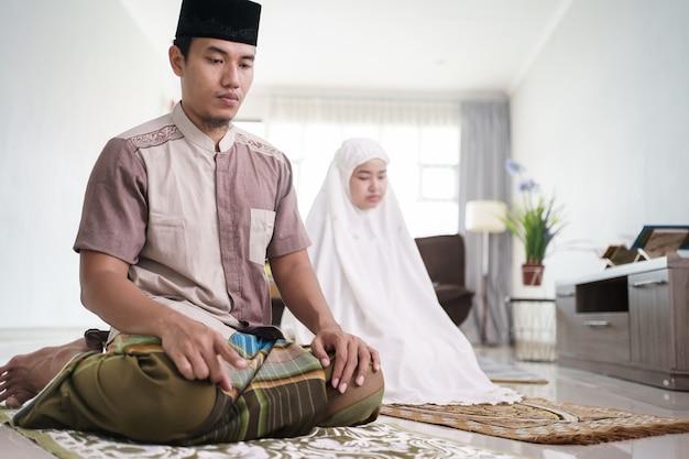 Азиатские мусульманские муж и жена вместе молятся дома