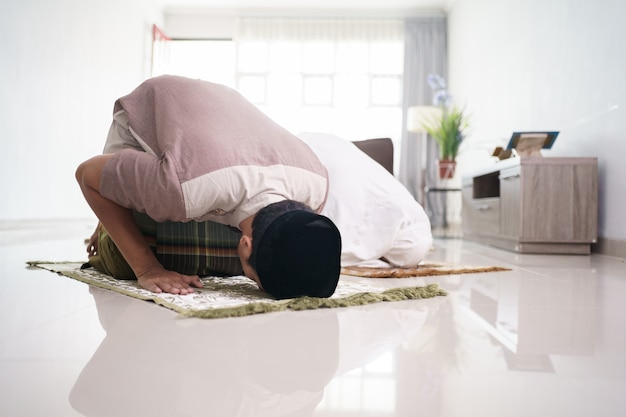 Asian muslim husband and wife praying jamaah together at home sujud