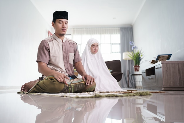 Asian muslim husband and wife praying jamaah together at home