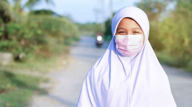 Asian muslim kid girl student wearing hijab and face mask to prevent covid-19
