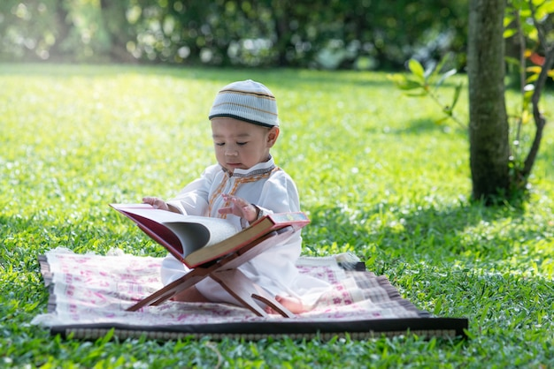 Asian muslim kid is reading the quran in the park, islam concept