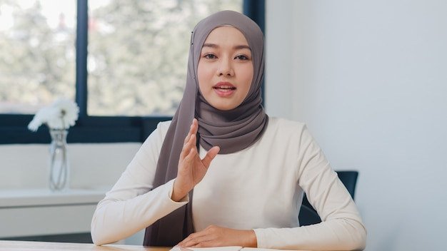 Asian muslim lady looking at camera talk to colleagues about plan in video call in new normal office.