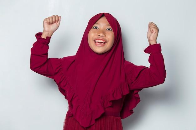 큰 성공을 표현하는 승리를 축하하는 행복하고 흥분된 아시아 이슬람 소녀