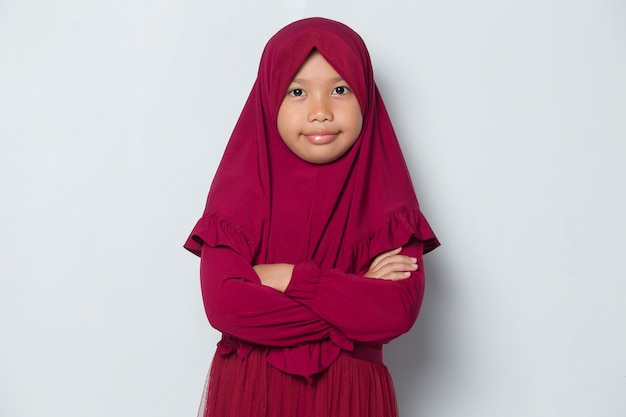 Asian muslim little girl in head scarf smile with arms crossed