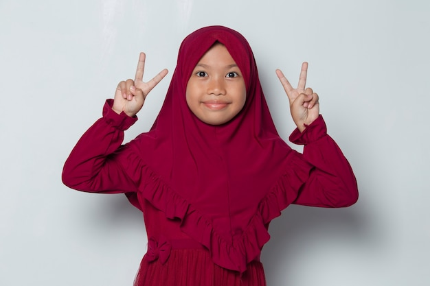 Asian muslim little girl in hijab showing peace or victory hand gesture