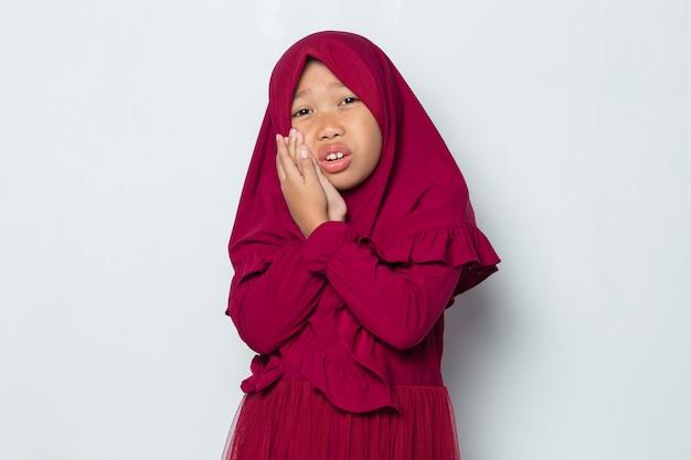 歯痛の痛みに苦しんでいる女性の歯痛の肖像画を持つアジアのイスラム教徒の少女