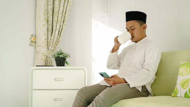 アジアのイスラム教徒の男性は彼の携帯電話で遊んでいる間飲み物を楽しんで礼拝を終了します