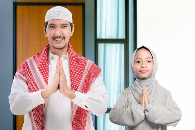 Asian muslim man and girl standing with greeting gesture in front of home