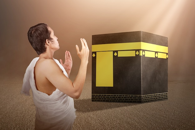 Asian muslim man in ihram clothes standing and praying in front of the kaaba with sunlight background