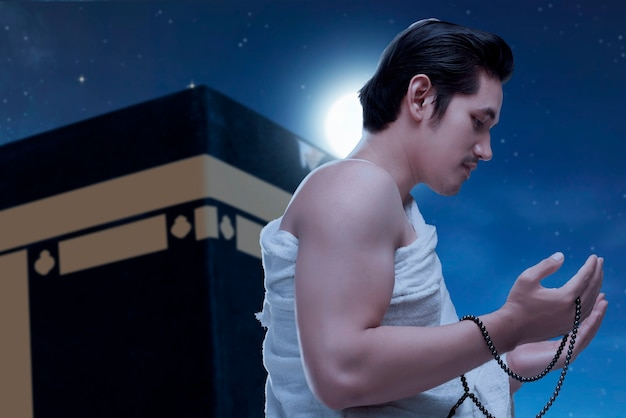 Asian muslim man in ihram clothes standing and praying with prayer beads with kaaba and night scene background