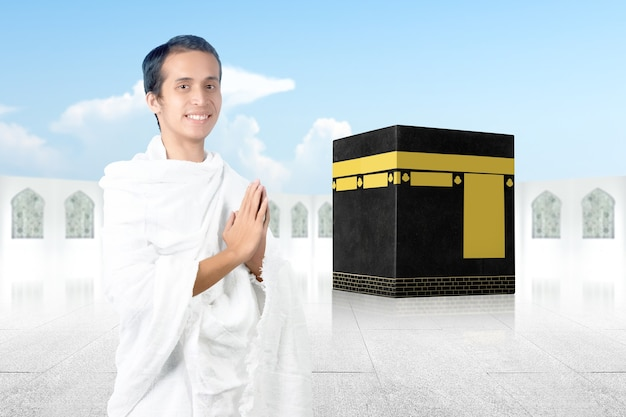 Asian muslim man in ihram clothes standing with greetings gesture with kaaba background