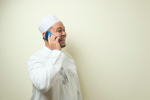 Азиатский мусульманин выглядит счастливым, когда ему звонит его брат. мужчина отметил курбан-байрам уверенным жестом