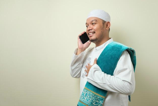 Азиатский мусульманин выглядит счастливым, когда ему звонит брат