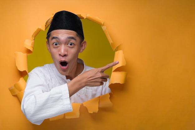 아시아 무슬림 남자는 충격을받은 얼굴로 찢어진 노란색 종이 구멍을 통해 포즈를 취하고, 두개골 모자와 함께 이슬람 천을 입고 복사 공간을 가리키는 뭔가를 제시합니다.